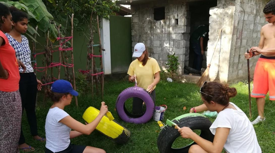 Childcare volunteers in Sri Lanka paint tyres for a multi-sensory garden at their Childcare placement.